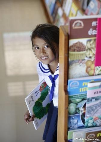 日本から届いた絵本を抱えるカンボジアの少女